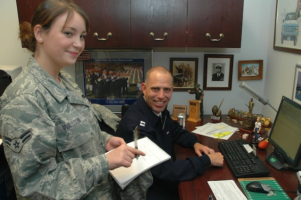 Airman 1st Class Anna M. Wasson, 11th Operations Group, speaks with Capt. Michael D. Fanton, U.S. Air Force Honor Guard, about creating e-mail accounts for incoming Airmen Sept. 16 at the Honor Guard complex. Airman Wasson was coined Sept. 15 during a wing stand-up by Col. Jon A. Roop, 11th Wing commander, for spearheading the validation of 450 network accounts and being named the 11th Wing Information Manager of the Quarter. (U.S. Air Force photo by Senior Airman Tim Chacon)