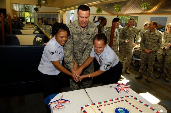 Col. Steven Shepro (center), 316th Wing commander, along with Airman Tiffany Barker (left), 316th Operations Support Squadron, and Chief Master Sgt. Lisa Haggett, 316th Force Support Squadron Superintendent, cut a birthday cake at the Freedom Hall Dining Facility Thursday. September 18 commemorated the Air Force's 61st birthday. Airman Barker is the newest Airman on Andrews, while Chief Haggett is Andrews' most seasoned career Airman. (USAF photo by Senior Airman Steven R. Doty)