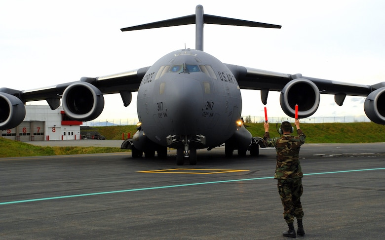 Kevin McElhoes, a C-17 crew chief with the 176th Wing's 249th Airlift Squadron, guides a Mississippi Air National Guard C-17 onto the flightline at Kulis Air National Guard Base, Alaska on Sept. 17, 2008. The C-17 Globemaster III carried two PaveHawk helicopters and their crews from the wing's 210th Rescue Squadron; and a group of pararescuers from the wing's 212th Rescue Squadron. The wing members deployed to the Gulf Coast region Sept. 1 to perform search-and-rescue operations in the aftermath of hurricanes Gustav and Ike. They were credited saving 16 lives during the mission.