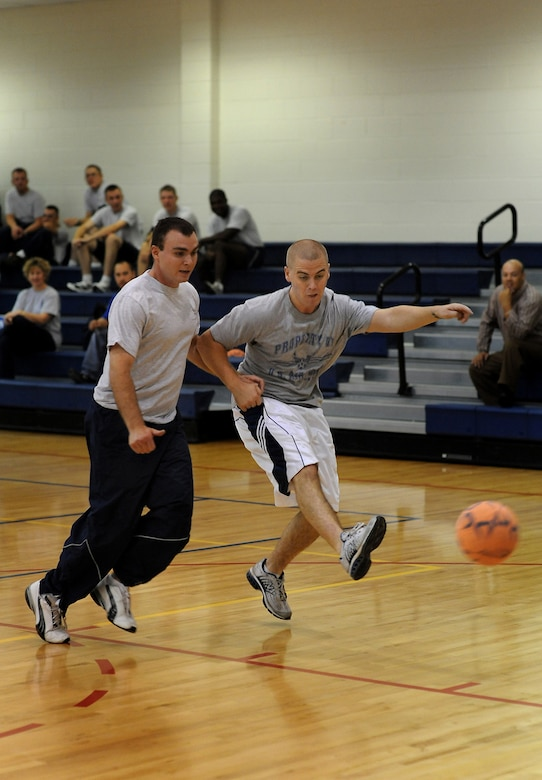 BUCKLEY AIR FORCE BASE, Colo. -- Nathan Smith, 460th CPTS, kicks the ball past a defender during an indoor soccer game at the Team Buckley Sports and Field Day, Sept. 12, at the Fitness Center during the Team Buckley Sports and Field Day. Events were originally scheduled to take place outside, but inclement weather forced sports day inside. Indoor soccer was played in place of ultimate frisbee. (U.S. Air Force photo by Senior Airman Steven Czyz)