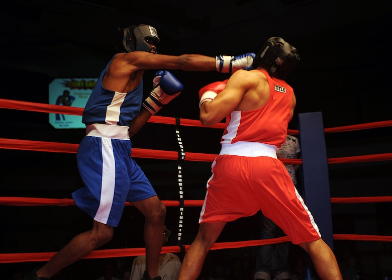 "Senior Airman Darius Jones, 49th Operations Support Squadron, lands a punch on Airman 1st Class Willie Bivins, 49th Maintenance Squadron, during their boxing match at the ""Raptor Rumble 2,"" Sept. 12. Airman Jones and Airman Bivins fought in the 160 pound weight class. (U.S Air Force photo/ Airman 1st Class DeAndre Curtiss)"
