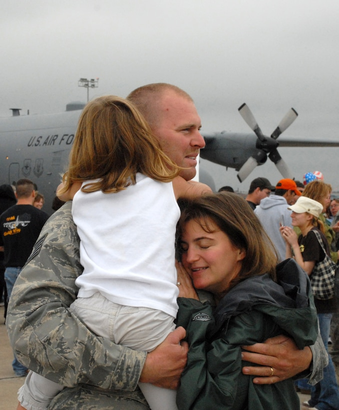 NIAGARA FALLS AIR RESERVE STATION, N.Y. -- Tech. Sgt. Vincent Gustafson, a pavements and equipment operator for the 914th Civil Engineering Squadron gets a reassuring hug from his wife and daughter that it's good to be home.  Gustafson was among 17 Air Force Reservists who recently arrived home from Bagram Air Base, Afghanistan.  These reservists  were deployed for approximately six months.  The group, part of an operation and maintenance team, were responsible for building and renovating facilities for the Army and other forward operating locations.  (U.S. Air Force photo/Master Sgt. Peter Borys)