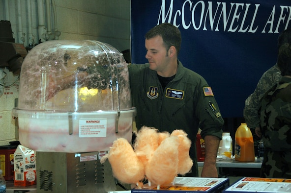 Staff Sgt. Jacob Cross reaches into a cotton candy machine during the 931st Air Refueling Group Family Day Picnic on Sept. 14.  Sergeant Cross, a KC-135 boom operator assigned the 18th Air Refueling Squadron, was one of the many 931st Airmen who volunteered to help during the picnic. (U.S. Air Force photo/Senior Airman Connor Burkhard)