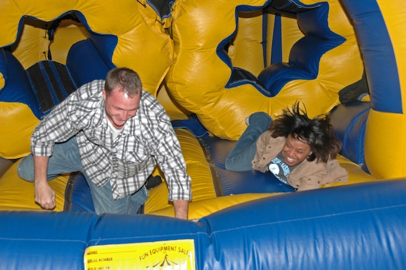 Staff Sgt. Wally Brannen and Senior Airman Tamara Wilson reach the finish of an inflatable obstacle course set up for old and young to enjoy during the 931st Air Refueling Group Family Day Picnic on Sept. 14. Both Airmen are assigned to the 931st Aerospace Medicine Flight. (U.S. Air Force photo/Senior Airman Connor Burkhard)