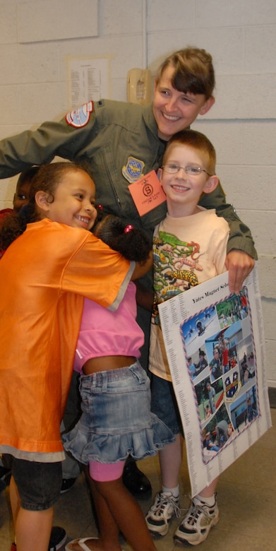 First Lt. Kelly Williams gets a group hug from students at Yates Elementary School. The school presented the volunteers with gifts and lunch to say thank you for all the work they've done. (U.S. Air Foce photo by Master Sgt. Christine Wood)