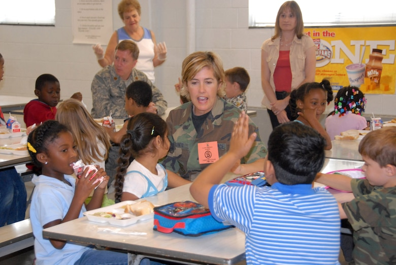 Master Sgt. Amy Giaquinto talks with students at Yates Elementary School during their lunch. (U.S. Air Foce photo by Master Sgt. Christine Wood)