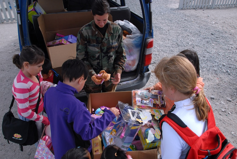 Master Sgt. Kelly Archambeault hands out toys to students in Greenland. The toys were donated to Stratton from Toys R Us.  (U.S. Air Force photo by Master Sgt. Christine Wood)