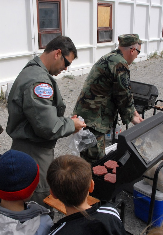 Kids wait patiently as Tech. Sgt. Michael Spiak (left) and Master Sgt. Pete Latniak grill some hamburgers during a community day 109th Airlift Wing members organized for the Greenland school. (U.S. Air Force photo by Master Sgt. Christine Wood)