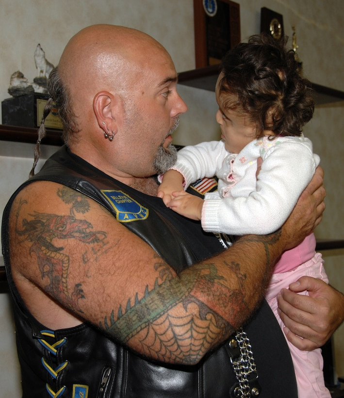James Whitmire, president for Bellevue's Chapter of the American Veterans Motorcycle Club, spends some time with Lorilei Todd, daughter of 1st Lt. Matthew and Monica Todd, recently. The AVMC raises money each year through a poker run to donate to military families with hardships. (U.S. Air Force Photo By Kendra Williams)