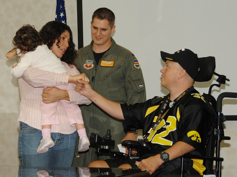 Monica Todd, her husband 1st Lt. Matthew Todd and daughter Lorilei, a special needs child, meet John Weinburgh, a disabled Army veteran, during a special ceremony recently. Both the Todd family and Mr. Weinburgh received donation from the Bellevue Chapter of the American Veterans Motorcycle Club. The AVMC raises money each year through a poker run to donate to military members and their families facing hardships. (U.S. Air Force Photo By Kendra Williams)