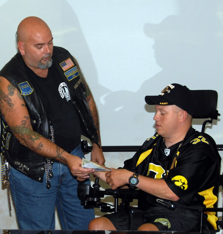 James Whitmire, president of Bellevue's Chapter of the American Veterans Motorcycle Club, presents a donation to John Weinburgh, a disabled Army veteran, recently.  Each year the AMVC's Bellevue Chapter raises money during its poker run to help military families in need. (U.S. Air Force Photo By Kendra Williams)