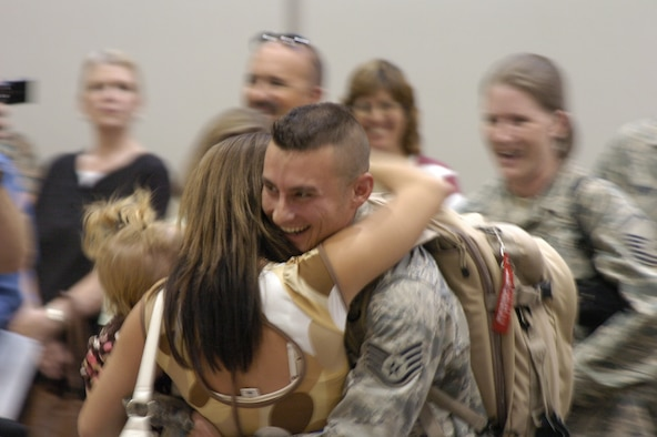 Staff Sgt. James Clark greets his wife at the Salt Lake International Airport on Sept. 11 as he and other members of the 75th Logistics Readiness Squadron return from a deployment. Members of their families, along with Col. Linda Medler, 75th Air Base Wing commander, were on hand to greet them.