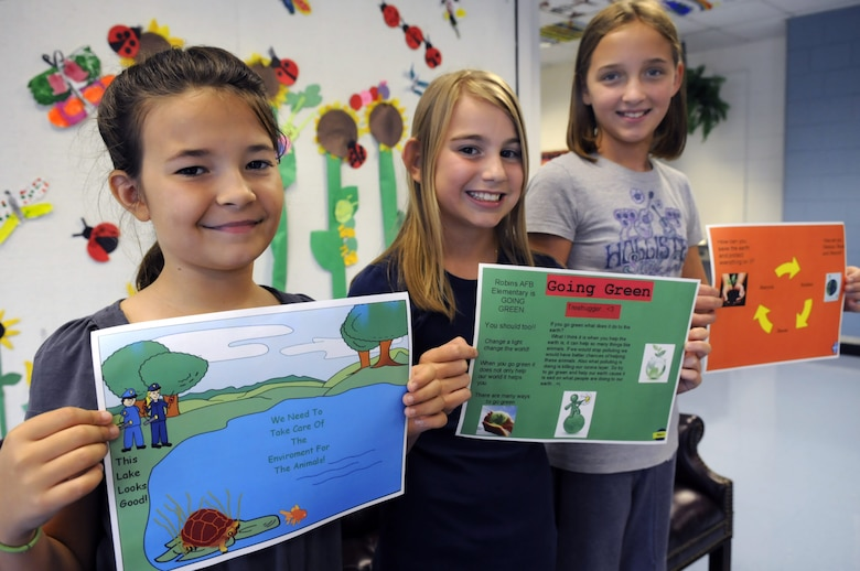 Alyssa Toellner, 4th grade, Brittany Fiveash and Kelsey Badgett, 6th grade, show off their Going Green advertisements. U. S. Air Force photo by Sue Sapp