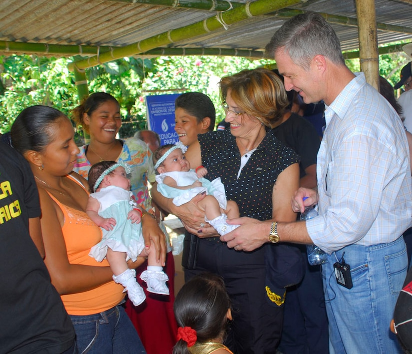 Janina Del Verchio, Costa Rica Minister of Public Security, and Peter Cianchette, U.S. Ambassador to Costa Rica, talk with a family who  received help from the medical readiness exercise in La Pena, Costa Rica. The family, who recently had twins, had received help from the Costa Rica Department of Safety when the twins were born had come back to say thank you and participate in the MEDRETE.(U.S. Air Force photo by Staff Sgt. Joel Mease)