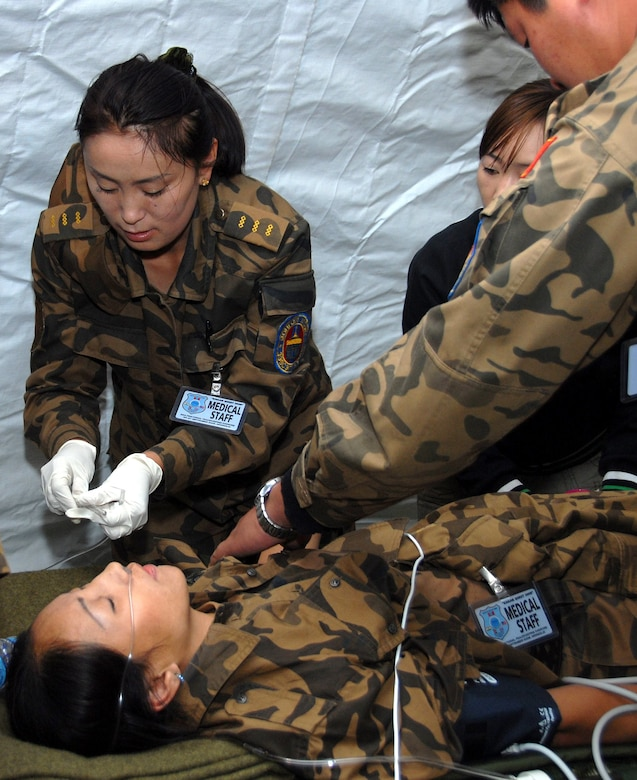 Mongolian Army medical personnel react to a real-world scenario when one of their medics fainted prior to a mock casualty scenario with Alaska Army National Guard. The training utilized the Mongolians' new Expeditionary Medical System (EMEDS) at the field training exercise Khaan Quest 2008, a United Nations multinational peace support exercise at Camp Five Hills Training Center near Ulaan Baatar, Mongolia. Alaska Air National Guard Photo by MSgt Jules Barklow