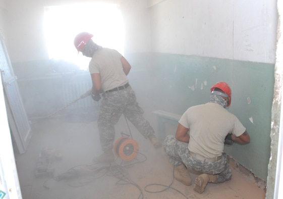Staff Sergeant Lawrence Pinheiro, carpenter, and Sergeant Joey Fernandez, carpenter, amidst a cloud of dust in the school dormitory in Alton Bulaag, Mongolia, where a renovation project by the 871st Engineering Battalion, Wailuku, Hawaii is underway. The local school dormitory had last been renovated in 1961. The Army Guard plumbers, electricians, masons and carpenters began overhauling windows, doors, paint and flooring on Sept. 4, 2008, with a deadline for completion of Sept. 21. They renovations were part of the field-training exercise Khaan Quest 2008, a United Nations multinational peace support exercise in Mongolia at Camp Five Hills Training Center near Ulaan Baatar. Alaska Air National Guard photo by MSgt. Jules Barklow.