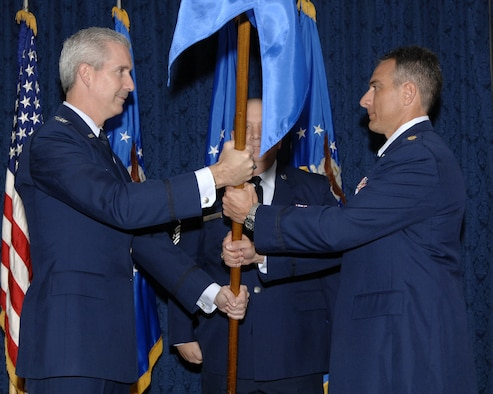 Col. Jon A. Roop, 11th Wing commander, passes the guidon to Maj. Jason Kobylski, 11th Comptroller Squadron commander, Oct. 23 during an assumption of command ceremony in the Bolling Clubs. Previously a directorate of the 11th Wing, the new squadron is 32 members strong and will be relocating from building 5681 to building P-20, room 240. The relocation is planned for late October to early November. (U.S. Air Force photo by Staff Sgt. Raymond Mills)