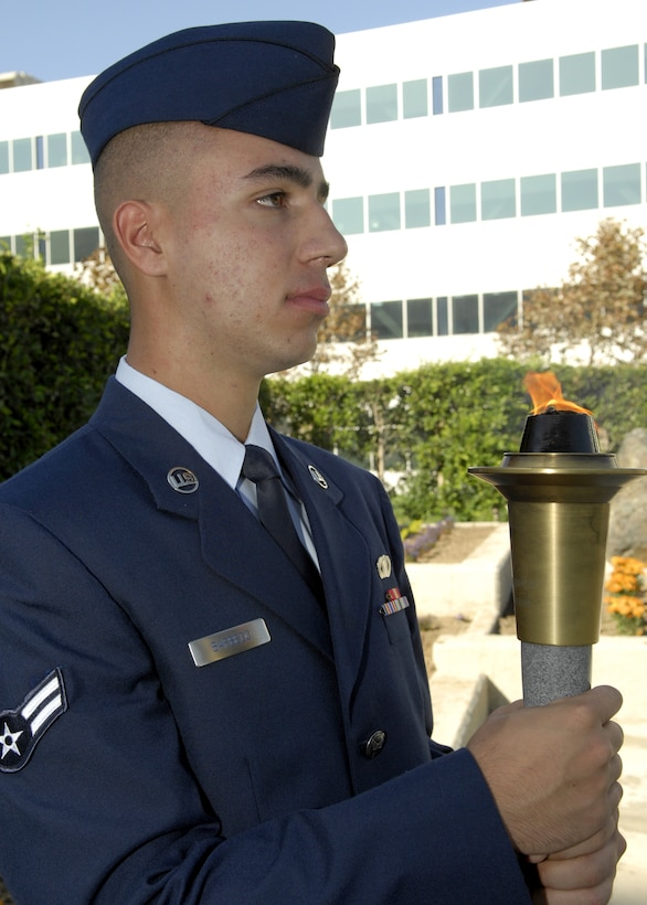 Airman 1st Class Turkha Barbedo, 61st Air Base Wing Financial Management, represented all the men and women of Space and Missile Systems Center as he holds the torch during the POW/MIA Wreath Laying Ceremony at the Schiever Space Complex courtyard, Sep. 19. The ceremony was preceded by a 24-hour torch relay commemorating the National POW/MIA Recognition Day, which more than 180 military, civilian, contractor, and family members from Los Angeles Air Force Base participated. (Photo by Stephen Schester)