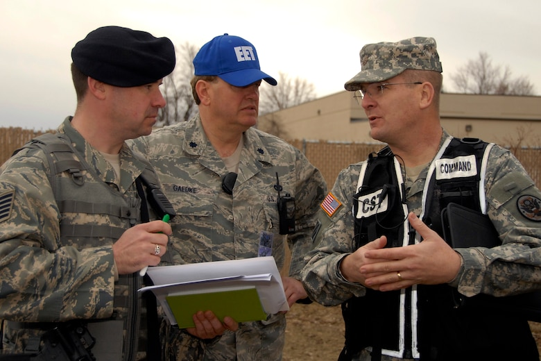 "Tech Sgt. Paul Opper, 115th Security Forces Squadron, Lt. Col. John Gaedke, 115th Mission Support Group, and Maj. Tim Covington, 54th Civil Support Team, discuss various response methods to a ""suspicious"" package during an exercise here March 18. The joint exercise included many different units on Truax Field as well as the U.S. Postal Service, Federal Bureau of Investigation and the 54th Civil Support Team. (U.S. Air Force Photo by Staff Sgt. Jon LaDue)"