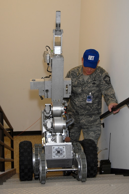 Senior Master Sgt. Edward Smith, 115th Explosive Ordnance Disposal Flight and Exercise Evaluation Team member, walks behind the F-6A Andros hazardous duty robot that was used to give critical intelligence to responding forces during a suspicious package exercise held at here March 18. The joint exercise included many different units on Truax Field as well as the U.S. Postal Service, Federal Bureau of Investigation and the 54th Civil Support Team. (U.S. Air Force Photo by Master Sgt. Dan Richardson)