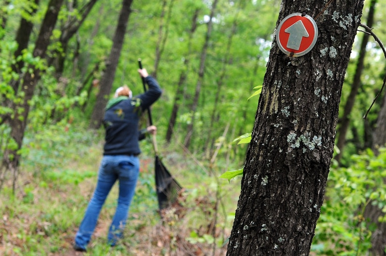 A trail restoration volunteer rakes leaves from the path of the Big Tree Hiking Trail. The trail is a total of 10 miles in length, volunteers hand raked the entire trail.(U.S. Air Force photo by Senior Airman Joanna M. Kresge)