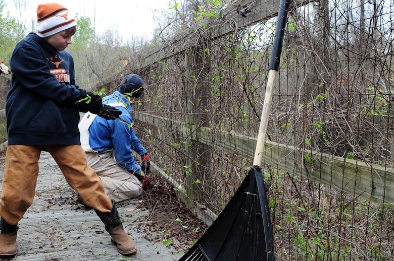 Trail restoration volunteers remove overgrown vines from a bridge along the Big Tree Hiking Trail. The bridge is over 580 feet long and weaves through swamp areas along the trail. (U.S. Air Force photo by Senior Airman Joanna M. Kresge)