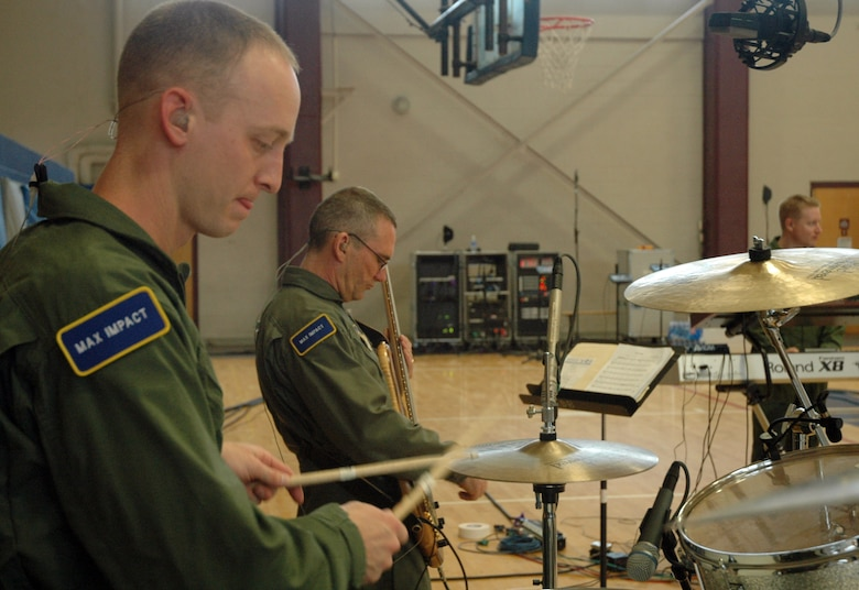 Master Sgt. Dennis Hoffman plays the drums while Master Sgt. Dave Foster strums his bass March 31 during a Max Impact performance March 31 on Maxwell Air Force Base, Ala. (U.S. Air Force photo by Senior Airman R. Michael Longoria)