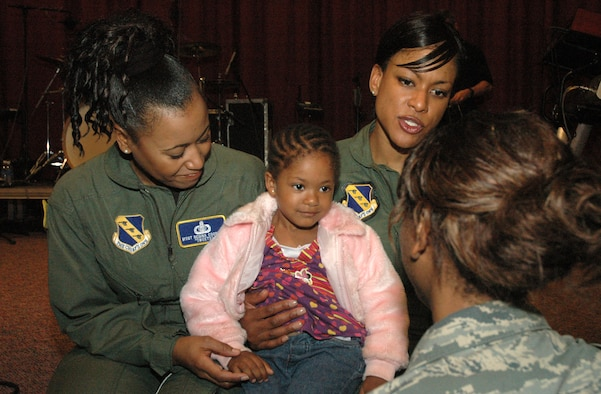 Master Sgts. Regina Coonrod and Shani Prewitt, members from the United States Air Force Band's premier rock group, talk to Airman 1st Class Fatimah Shareef-Malik and her four year-old daughter Lailah, March 27 after a Max Impact performance at Robin Air Force Base, Ga. (U.S. Air Force photo by Senior Airman R. Michael Longoria)