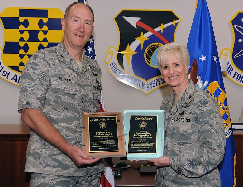 Col. Stephen Pluntze, Defense Meteorological Satellite Systems Group commander, presents to  Col. Anita Latin, 61st Air Base Wing commander, the Combined Federal Campaign's Golden Wings and Emerald awards on behalf of Los Angeles Air Force Base. Personnel here contributed more than $300,000 to local, national and international charities during last year's CFC campaign. (Photo by Joe Juarez)