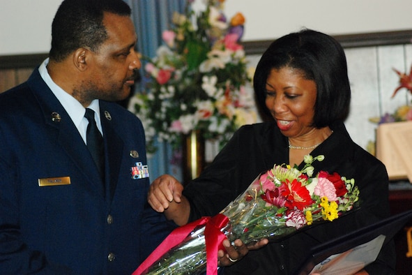 Tech. Sgt. Ronald Palmer presents a bouquet of flowers to his wife in honor of her support during his 20-plus years of service as an air reserve technician in the 94th Aerospace Ground Equipment section of the 94th Aircraft Maintenance Flight.  (U.S. Air Force photo/Tech. Sgt. Robert Martin)