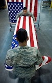 Shipping Specialists Staff Sgt. Star Samuels (front) and Tech. Sgt. Willard Rico place a U.S. flag over a casket March 31 during a dry run of shipping process procedures for the dignified transfer of remains at the Charles C. Carson Center for Mortuary Affairs, Dover Air Force Base, Del.  The center is the Defense Department's largest joint-service mortuary facility and the only one in the continental United States. Sergeant Samuels is deployed from the 43rd Force Support Squadron at Pope AFB, N.C.  Sergeant Rico is deployed from the 60th FSS, Travis AFB, Calif.  (U.S. Air Force photo/Staff Sgt. Bennie J. Davis III)