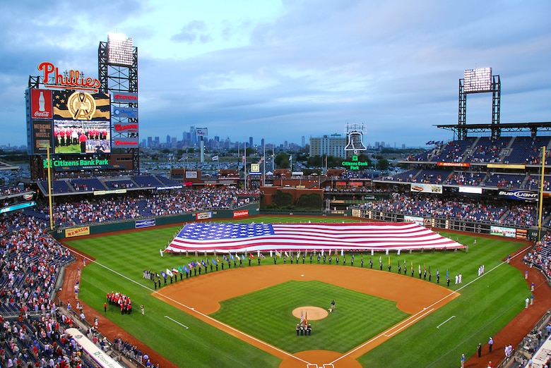 Servicemen and women from the 111th Fighter Wing, Pa. Army National Guard, as well as active duty Navy and Marine Corp members unfurled a 120-by-250 foot American Flag across the outfield of Citizens Bank Park during a Patriots Day ceremony Sept. 11 before the game. While the center field size flag was being opened, volunteer firefighters from Philadelphia, Delaware County and Warminster fire companies marched around the bases each carrying a state flag.