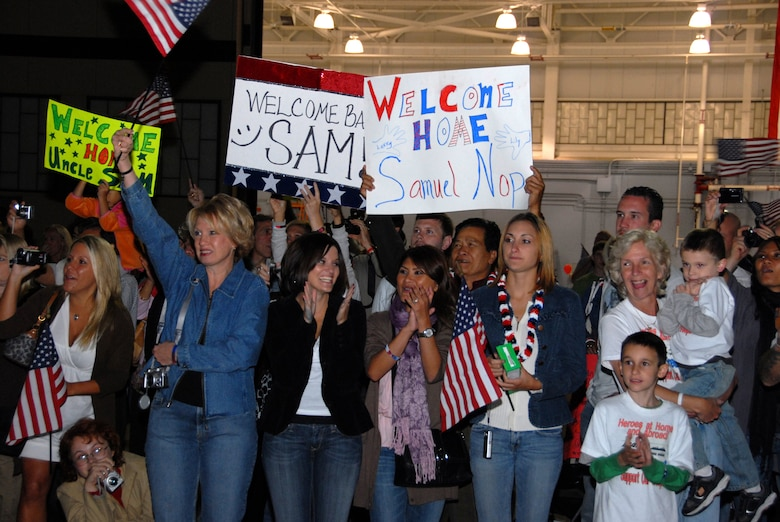 Friends and family cheer, wave flags and welcome home signs as guardsmen from the 111th Fighter Wing, Pa. Air National Guard, return to Willow Grove ARS, Pa. Sept. 20 from a deployment to Afghanistan.