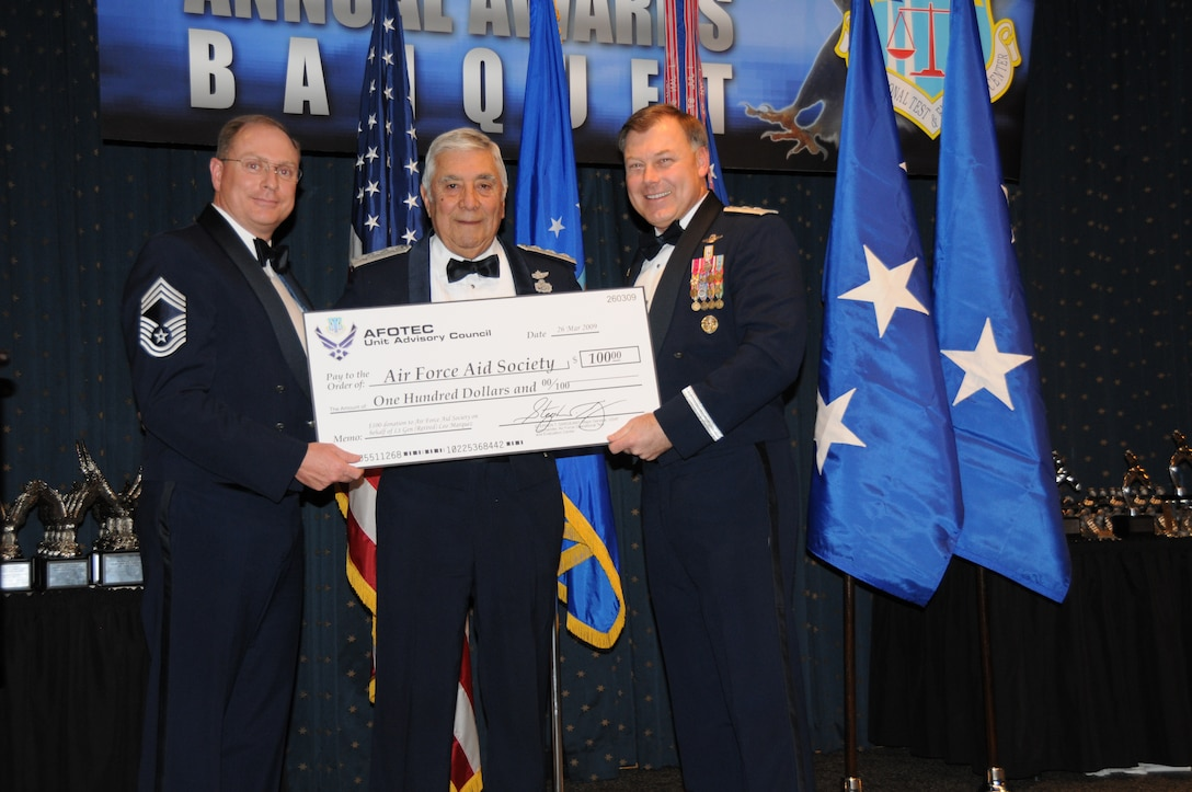 (Left to right) Air Force Operational Test and Evaluation Center Commander Maj. Gen. Stephen T. Sargeant presents Lt. Gen. Leo Marquez (retired) a donation to the Air Force Aid Society in his name in appreciation for being a guest speaker at the March 26, 2009 AFOTEC Annual Awards Banquet. AFOTEC Chief Enlisted Manager CMSgt. Kelly Branscom assists in the presentation. More than 65 AFOTEC member were recognized as outstanding performers for 2008.