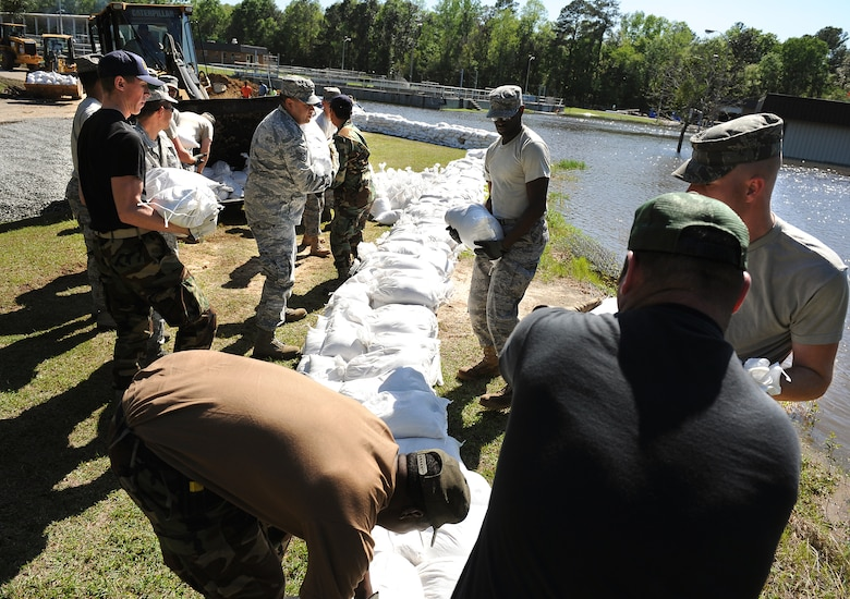 MOODY AIR FORCE BASE, Ga. -- Airmen from the 23rd Civil Engineer Squadron, stack sand bags to prevent flood damage at the Valdosta Wastewater Treatment Plant April 3. Due to flooding caused by heavy rain, the city requested on-site assistance from the 23rd CES to protect a vital lift-pump building. (U.S. Air Force illustration by Airman Joshua Green)