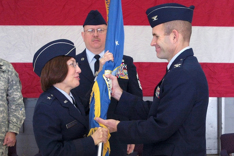 Incoming Commander of the 177th Fighter Wing Col. Robert C. Bolton (right), accepts the 177th's Colors from Brig. Gen. Maria Falca-Dodson (left), Commander, New Jersey Air National Guard, while 177th Command Chief Master Sgt. Michael R. Francis (center) observes during the Change of Command Ceremony held at the Wing on Feb. 8.  Prior to assuming command of the 177th, Col. Bolton served as the Wing's Operations Group Commander.  Photo by Tech. Sgt. Mark Olsen, 177FW/PA.