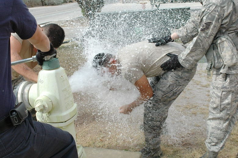 Senior Airman Joe De Vos finds relief after being sprayed with pepper spray in an open fire hydrant at the 162nd Fighter Wing in Tucson, Ariz., April 7. All Security Forces members who have not experienced the non-lethal agent are now required to learn its effects according to a new Air Force manual on the use of force. (Air National Guard photo by Capt. Gabe Johnson)