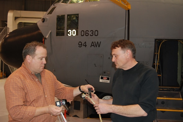 DOBBINS AIR RESERVE BASE,  Ga. -- Air Reserve Technician Dave Metroka, 94th Airlift Wing Avionics/Munitions Flight, right, and Greg Johnson, E.J.M. Aerospace Services from Crestview, Fla., inspect  a new switching system being installed in a Dobbins ARB C-130 aircraft during a test modification program April 7.  The modification should increase a pilots and co-pilots ability to dispense chaff and flares. (U.S. Air Force photo/Jim Weslowski)