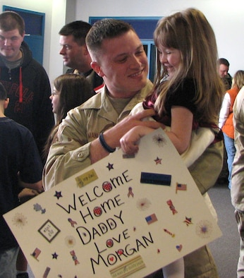 Staff Sgt. Stephen Manley, a Northeast Air Defense Sector Security Force member returning from deployment, smiles at his daughter Morgan at the Syracuse International Airport March 14. In the unit's largest deployment ever, nearly 30 security force members deployed on a six-month tour to Manas Air Base, located in Kyrgyzstan, in September 2007.