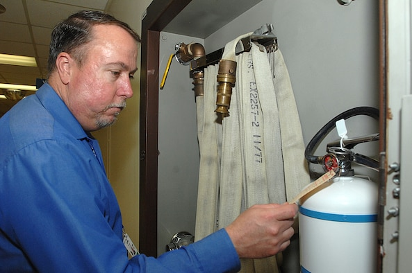 """Mr. Michael Griffith, 59 Medical Wing safety specialist, checks that the monthly fire extinguisher inspection is current  April 2, 2009 on one of the many extinguishers located throughout  Wilford Hall Medical Center.  Mr. Griffith won the Air Education and Training Command """"Well Done Award."""" (U.S. Air Force photo by Staff Sgt. Robert Barnett)"""