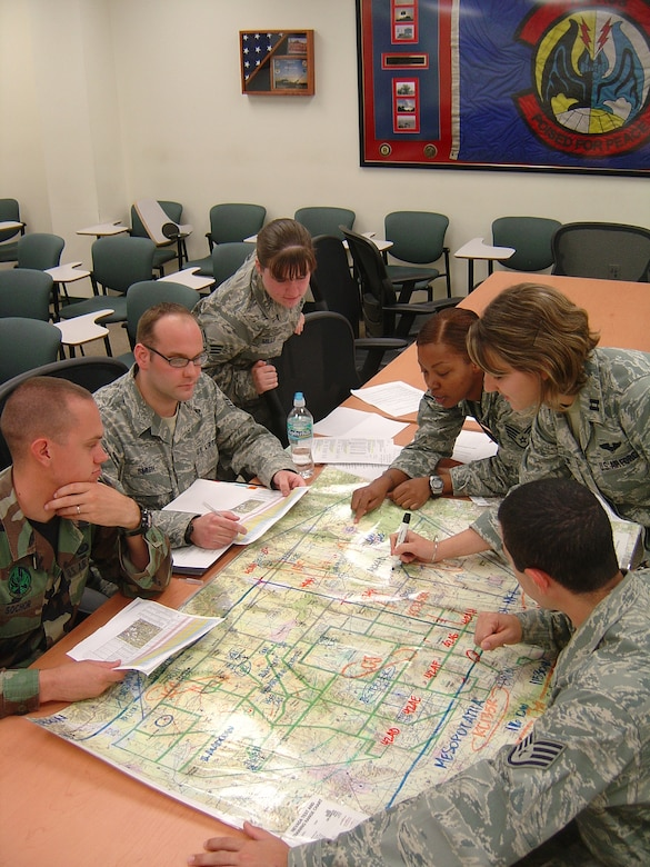 The 728th Air Control Squadron selected Turkey Shoot competition team review a map of the Nevada Test and Training Range, where the simulated war took place during a March exercise. From left to right are Airman 1st Class Robert Sochor, Staff Sgt. Andrew Smith, Senior Airman Lisa Mills, Staff Sgt. LaToya Johnson, Capt. Kisha Balling and Staff Sgt. Anthony Rigazio.