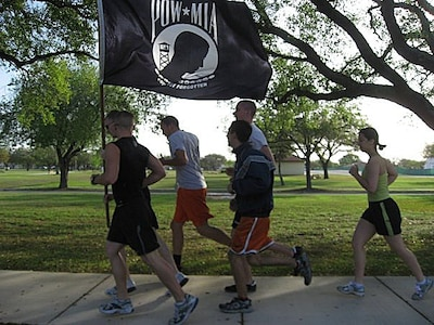 """Air Force ROTC cadets from Det. 842 at the University of Texas at San Antonio run passed Airman Heritage Park at Randolph Air Force Base, during the """"Taj to Tower, POW-MIA Run"""" April 4. The 70-mile run, sponsored by the Arnold Air Society, is held each year with the prospects of creating unity among different squadrons of AFROTC cadets at local colleges, as well as raising awareness of the sacrifices of past servicemembers to those traveling down Interstate 35 during the day of the run. This year three schools participated in the run; Det. 842, Det. 840 from Texas State University, and Det. 825 from the University of Texas, Austin.  (courtesy photo)"""