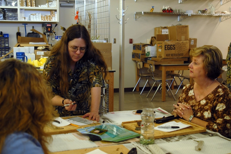 Teri McClure (center) explains the basics of stained glass designs to attendees at the Goodfellow Arts and Crafts Center's Fabulous First-Monday Art Extravaganza April 6. Ms. McClure, who has been working at the Arts and Crafts Center since 1989, learned the art of stained glass design in 1987. (U.S. Air Force photo by Airman 1st Class Anne Gathua)