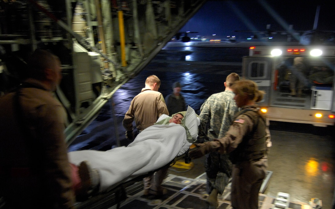 Members of the 455th Expeditonary Aeromedivac Flight carry Airman 1st Class, Brent Noah, 376th Expeditonary Aircraft Maintenance Squadron, Manas Air Base, Kyrgyzstan to an ambulance at Bagram Air Field, Afghanistan, March 26. Airman Noah dislocated his hip exercising at Manas a day before. (U.S. Air Force photo/ Senior Airman Erik Cardenas)(Released)