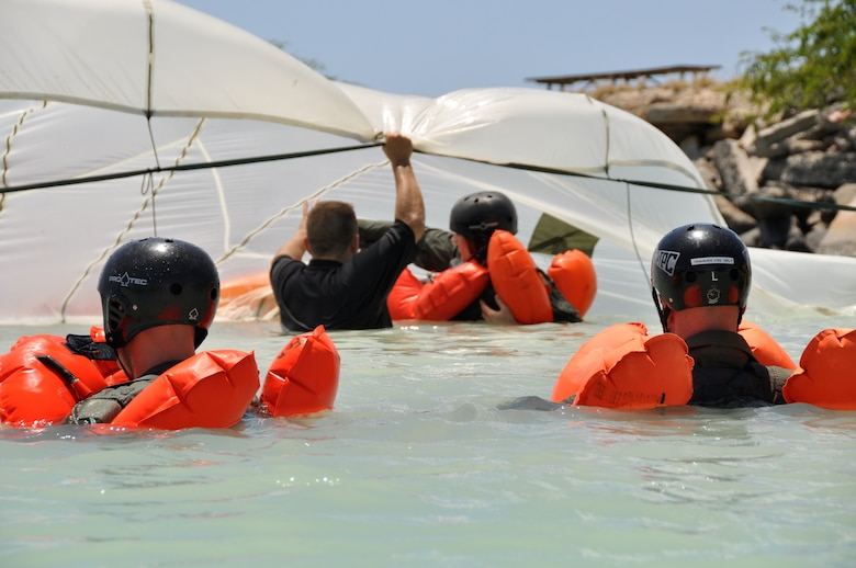 HICKAM AFB  -  U.S. Air Force Survival Evasion Resistance Escape Specialist Tech. Sgt. Sherwood Brown briefs an aircrew member on the correct way to swim under a parachute canopy during refresher water survival training on April 6, 2009 while in the waters adjacent to Hickam AFB, Hawaii . (U.S.  Air Force photo/Tech Sgt. Cohen A. Young)