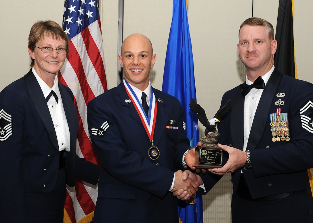 AURORA, Colo. -- Senior Airman John Fairman, 460th Operations Support Squadron, seen here with Chief Master Sgt. Gerrie McCoy, 460th Medical Group Superintendent, receives his John L. Levitow Award from Senior Master Sgt. Dean Harris, 460th Civil Engineer Squadron Operations Superintendent.  The Airman Leadership School graduated 12 future Air Force leaders from the Doubletree hotel here March 27. (U.S. Air Force photo by Senior Airman Erika Brooke)