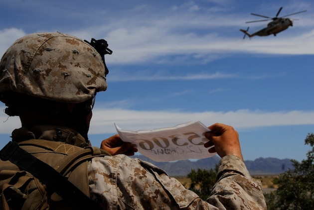 Sgt. Jared Leiss, a squad leader with 3rd Battalion, 9th Marine Regiment, shows his squad's number for the pilot of an MV-22 Osprey who picked up the Marines at during an air assault exercise, April 13, 2009, in a training area east of Marine Corps Air Station Yuma, Ariz. The Quincy, Ohio, native and his squad of approximately 10 Marines were transported to a landing zone in the Blue Mountain Airfield for a live-fire exercise and to secure the airfield. The Camp Lejeune, N.C., battalion is scheduled to conclude their training in Yuma with a battalion-sized helicopter-borne assault exercise in late April, the largest exercise of its type conducted in approximately 10 years.