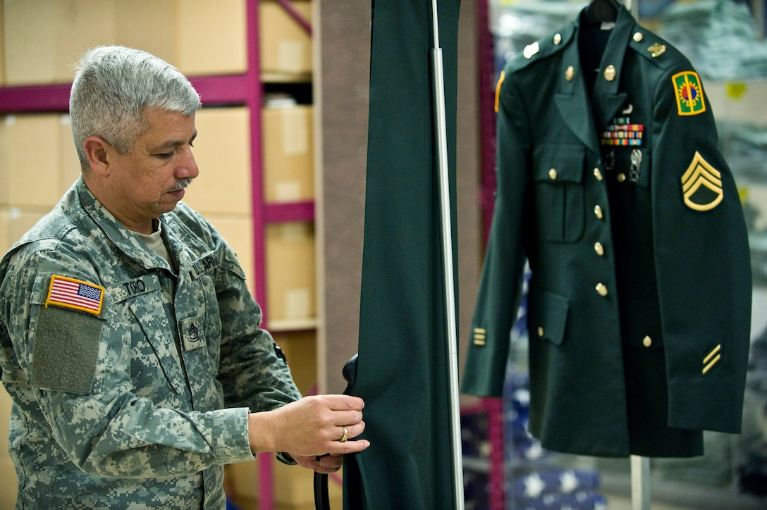 U.S. Army Sergeant First Class Jimmy Toro, a  mortuary affairs specialist, steam cleans the uniform of a fallen solider during preparation of the dignified transfer of remains process March 31. Sgt. Toro is on his third year-long voluntary deployment assisting the Air Force Mortuary Affairs Operations Center at Dover Air Force Base, Del. The servicemembers in the uniform section prepare uniforms for the fallen heroes and work with military escorts for the dignified-transfer-of-remains process.  Sergeant Toro is deployed from the U.S. Army Reserve, 311th Quartermaster Company in Puerto Rico. (U.S. Air Force photo/Staff Sgt. Bennie J. Davis III)