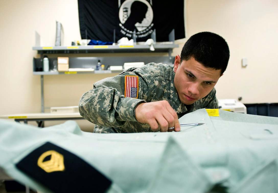 Specialist Xavier Gonzalez, a mortuary affairs specialist, prepares a U.S. Army service dress shirt for a fallen solider March 31. Servicemembers working in the uniform section of the Air Force Mortuary Affairs Operations Center at Dover Air Force Base, Del., prepare uniforms for the fallen heroes and work with military escorts for the dignified-transfer-of-remains process.  Specialist Gonzalez is deployed from the Army Reserve, 311th Quartermaster Company in Puerto Rico.  (U.S. Air Force photo/Staff Sgt. Bennie J. Davis III)