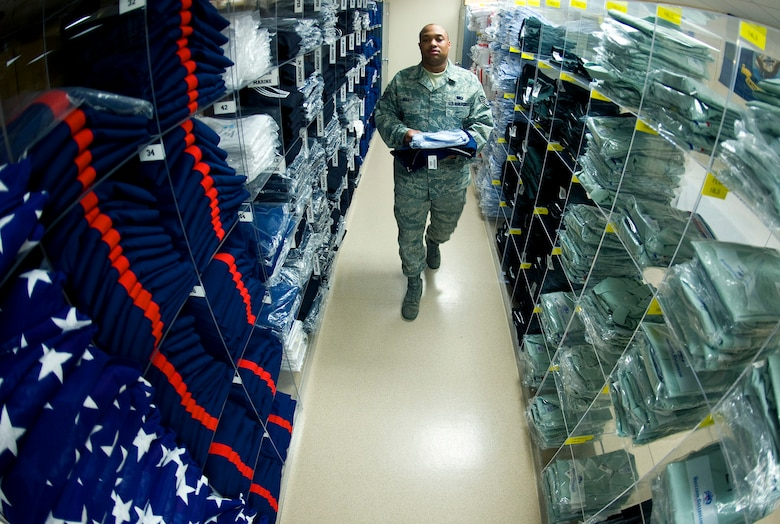 Staff Sgt. Charles Bell, a mortuary technician at the Air Force Mortuary Affairs Operations Center at Dover Air Force Base, Del., walks through rows of military service dress uniforms that are stored there for every rank and size. Sgt. Bell is the Air Force non-commisioned officer in charge of logistics and oversees ordering and stocking service dress uniforms and items for dignified transfer of remains.  (U.S. Air Force photo/Staff Sgt. Bennie J. Davis III)